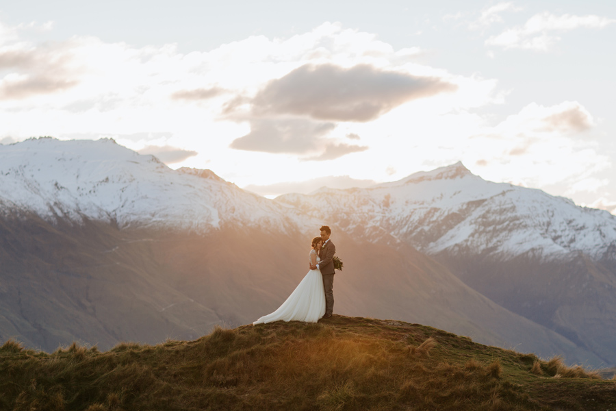 A couple embrace in the mountains, as the sun sets behind them. There are snow capped mountains in the background. With photography by Alpine Image Company