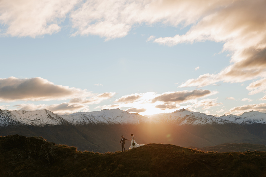 A groom leads his bride along a mountain ridgeline, on their Wanaka Elopement Wedding. There are snowcapped mountains in the background, and the sun is setting behind them. With photography by Alpine Image Company