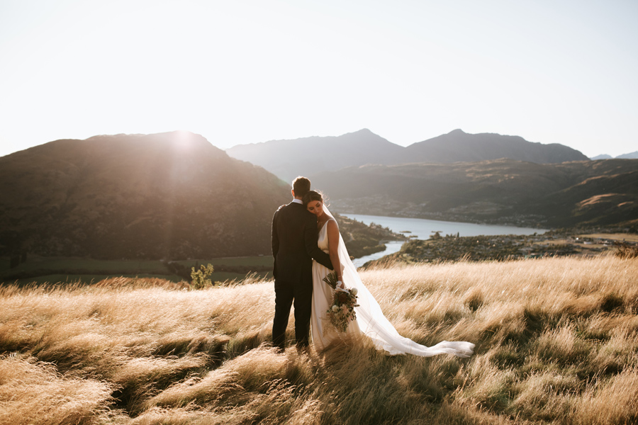 A bride rests her head against her husband, as they stand in a golden field on their Queenstown elopement wedding day. With photography by Alpine Image Company