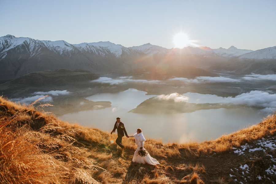 A man leads his bride up a ridgeline on their Wanaka elopement wedding. They are on a grassy mountain, and there is a lake and mountains in the background. With photography by Alpine Image Company