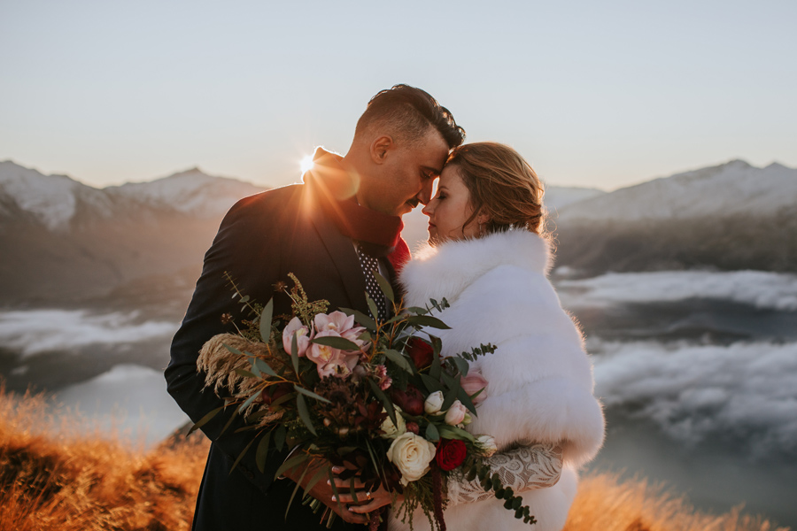 A couple put their heads together, as the sun sets behind them on their wanaka elopement wedding. There are mountains in the background and it is a blue sky wintery day. With photography by Alpine Image Company