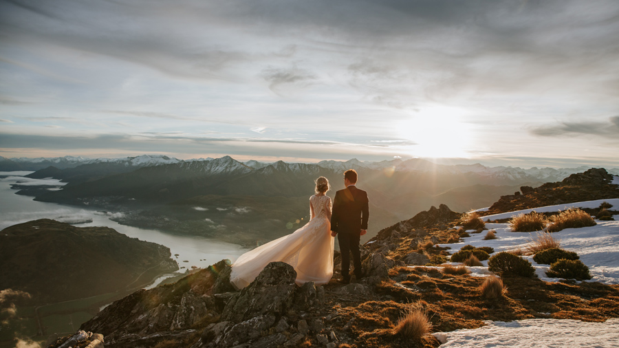 A couple stand high on a mountain on their Queenstown Elopement wedding. The sun is setting over the mountains in the distance, and they look out at the view. With photography by Alpine Image Company