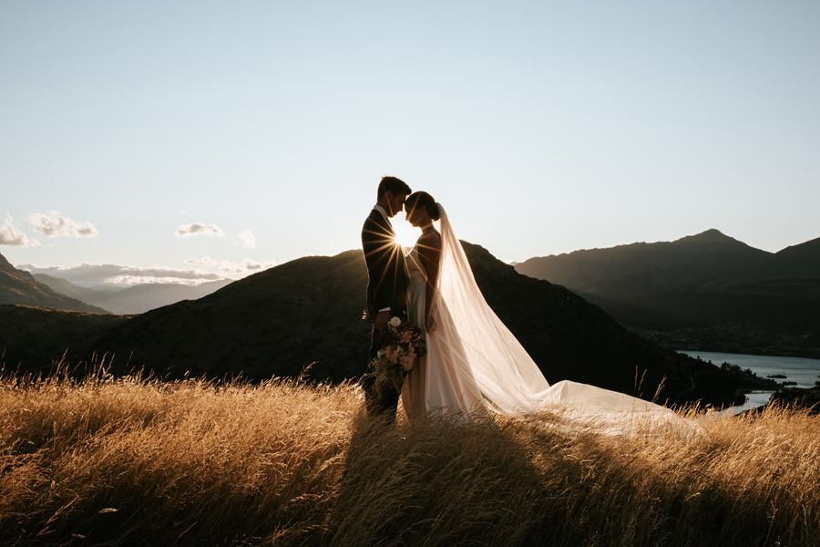 A couple stand in a golden field, with their bodies together. The sun sets behind them on their Queenstown elopement day. There are mountains in the distance. With photography by Alpine Image Company
