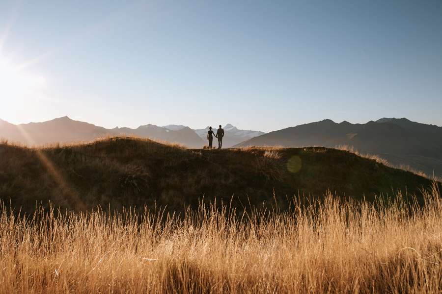 A couple on their Wanaka Elopement day. They stand on a mountain as the sun sets behind them. There is golden grass in the foreground, and mountain peaks in the distance. With photography by Alpine Image Company