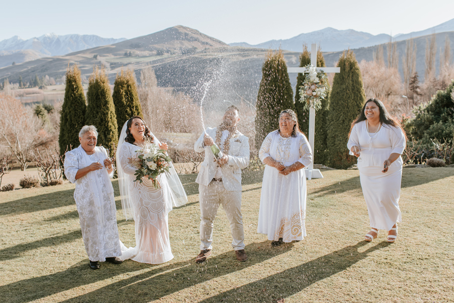 A groom pops the champagne bottle surrounded by family at Stoneridge Estate in Queenstown on their wedding day. Photography by Alpine Image Company.