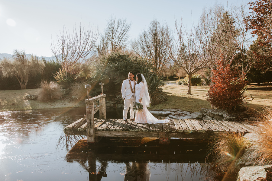 A newly married couple stand on a bridge over a pond at Stoneridge Estate Queenstown. Photography by Alpine Image Company.