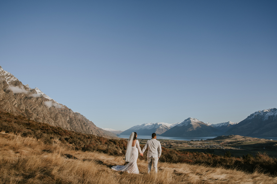 A married couple stand high above Queenstown, looking over the lake and mountains on their wedding day. Photography by Alpine Image Company.