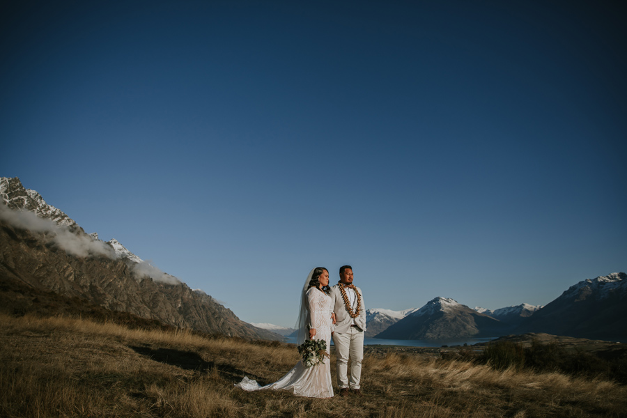 A deep blue sky and towering mountains surround a couple who stand hand in hand in Queenstown on their wedding day. Photography by Alpine Image Company