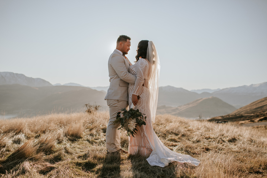 A newly married couple cuddle in the hills in Queenstown. The light is soft and warm. Photography by Alpine Image Company