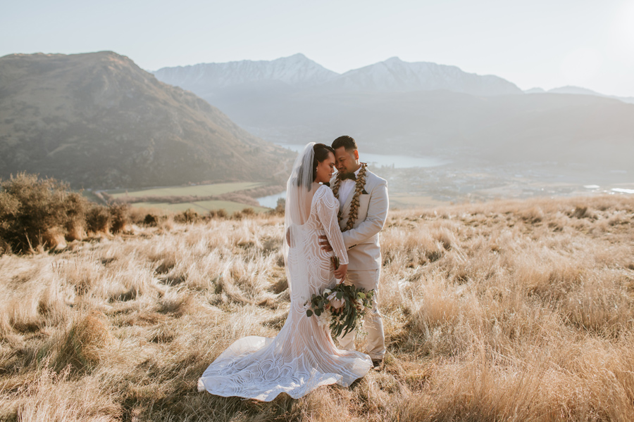 Standing in a field of long grass with golden light a couple rest their foreheads together. The river and mountains are visible in the background. Photography by Alpine Image Company.