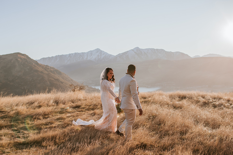 In the soft pink evening light a couple walk holding hands on their wedding day. You can see the lake and the Queenstown mountains. Photography by Alpine Image company.