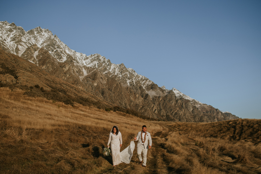 A groom holds his wives dress as they walk in the golden light. The sky is blue and the Remarkable mountains are behind them. Photography by Alpine Image Company.
