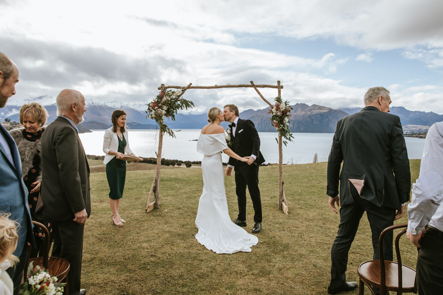 A bride and groom share a kiss in front of their wedding arch on their Wanaka Wedding Day. There are mountains and a lake in the background. With photography by Alpine Image Company
