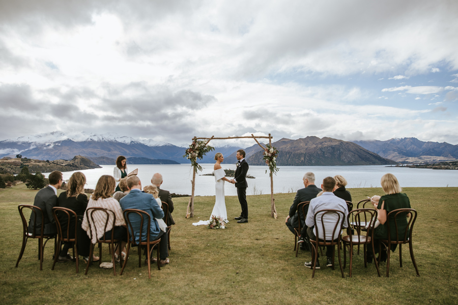 A couple stand in front of their wedding arch, on a hill. There are mountains and a lake in the background. Their wedding guests sit on chairs surrounding them. With photography by Alpine Image Company