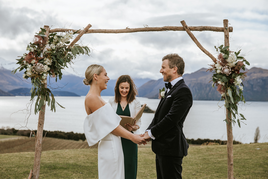 A bride and groom share a laugh together during the ceremony on their Wanaka wedding day. There are mountains and a lake behind them, and flowers on the arch. With photography by Alpine Image Company
