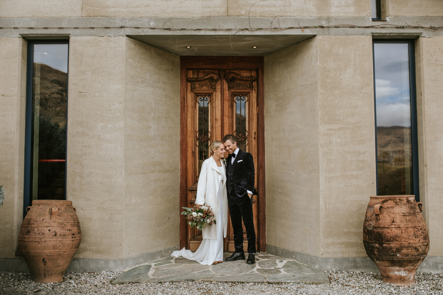 A couple rest their heads together in front of decorative wooden doors at their Rippon Vineyard wedding. With photography by Alpine Image Company