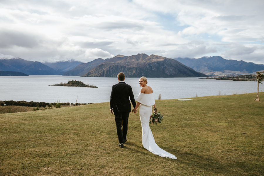 A couple walk away from the camera on their Rippon wedding day. There are mountains and a lake in the background, and the grass is a lush green. With photography by Alpine Image Company