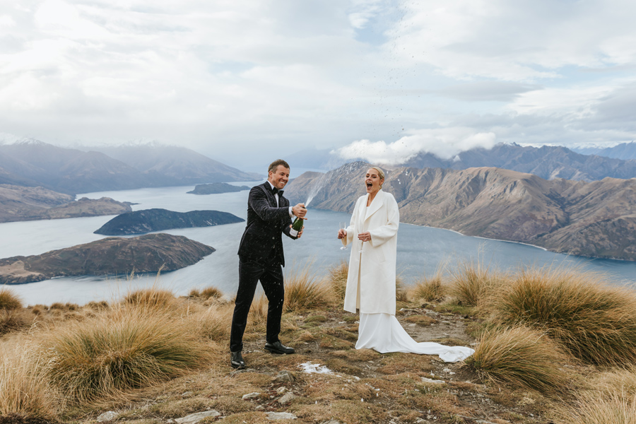 A couple pop a bottle of champagne on top of Coromandel Peak on their wanaka wedding day. There is a blue lake in the background, and mountains surround them. With photography by Alpine Image Company