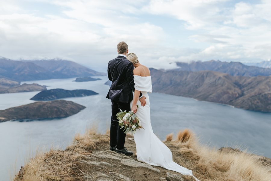 A couple rest their heads against each other as they look out from Coromandel peak on their Wanaka wedding day. There are lakes and mountains in the background, and clouds in the sky. With photography by Alpine Image Company