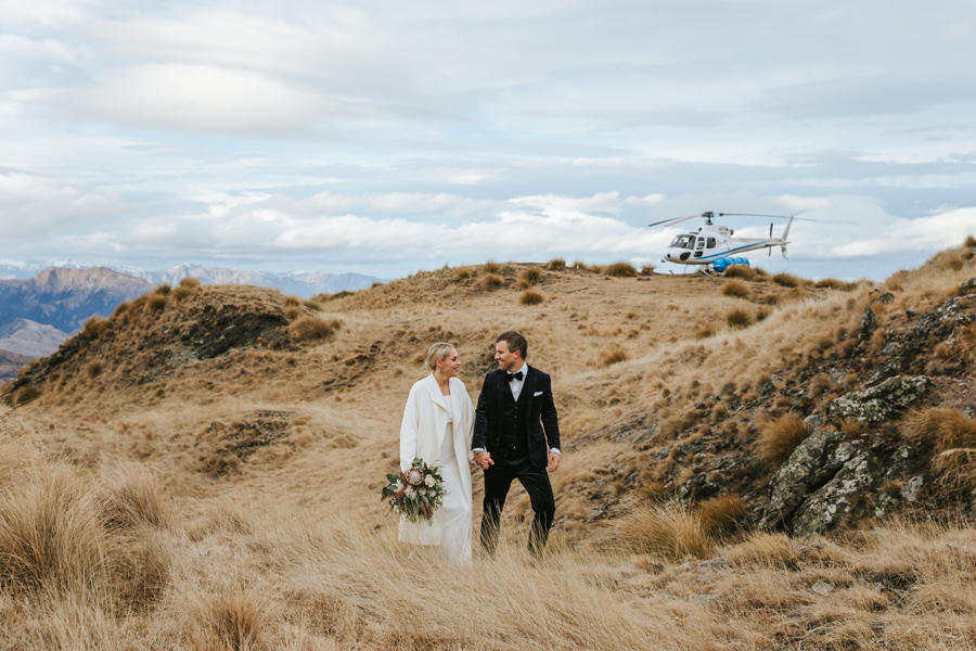 A couple walk through long grass in the mountain tops on their Wanaka wedding day. There are mountains and a helicopter in the background, and they look at each other, smiling. With photography by Alpine Image Company