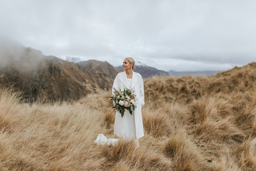 A bride stands in the mountains on her Wanaka wedding day. The glass is long and dry, and the clouds hang low in the background. With photography by Alpine Image Company