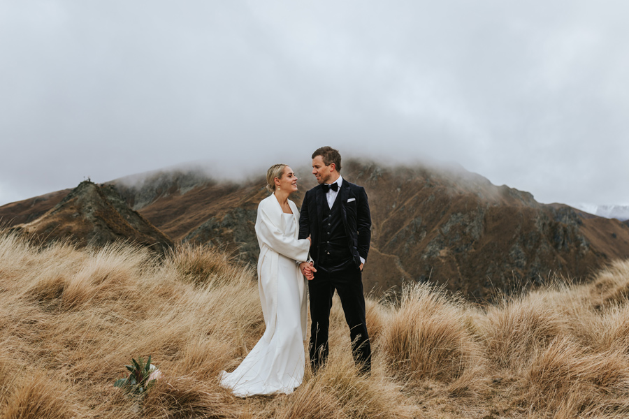 A bride and groom stand arm in arm in the mountains on their wanaka wedding day. There is a mountain in the background with low hanging cloud surrounding its peak. They smile at each other. With photography by Alpine Image Company