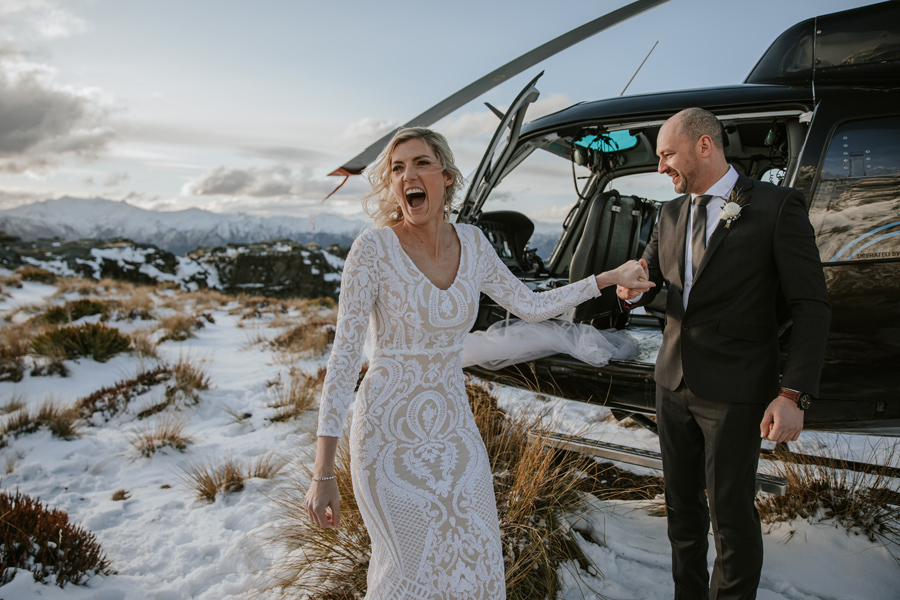 A bride laughs as she gets out of a helicopter on her Queenstown Wedding Day. There is snow on the ground behind her, and snow capped mountains in the distance. She holds her husbands hand. With photography by Alpine Image Company