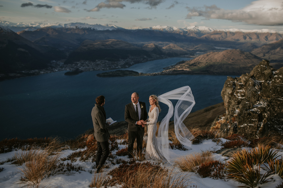 A bride and groom hold hands during their wedding ceremony, on their Queenstown Wedding Day. They are standing on a snowy mountain, overlooking Queenstown and Lake Wakitipu. The sky is blue and there are snow capped mountains in the distance. With photography by Alpine Image Company