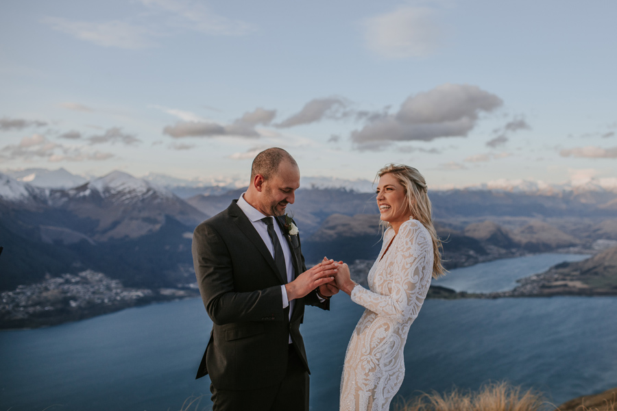 A groom puts a ring on his bride on their wedding day. They are standing on a mountain top with a lake in the background. The sky is blue and there are fluffy white clouds surrounding them.