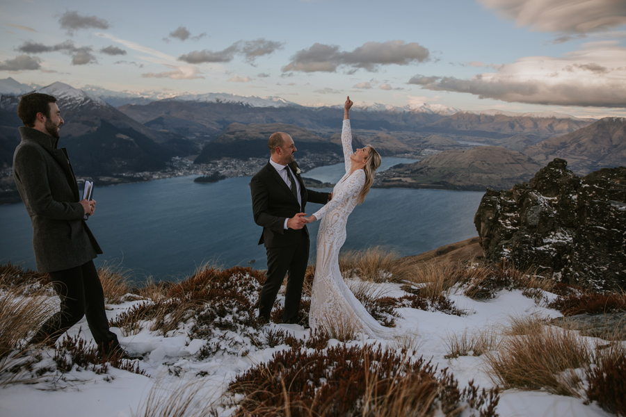 A bride raises her hand in the air in joy as she is married to her husband. They are standing on a mountain top, with a blue lake and snow capped mountains in the background.