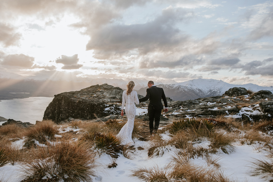 A bride and groom walk away from the camera. They are holding hands and the sun is setting behind them. They are on a snow capped mountain top, with a lake and mountains in the background.