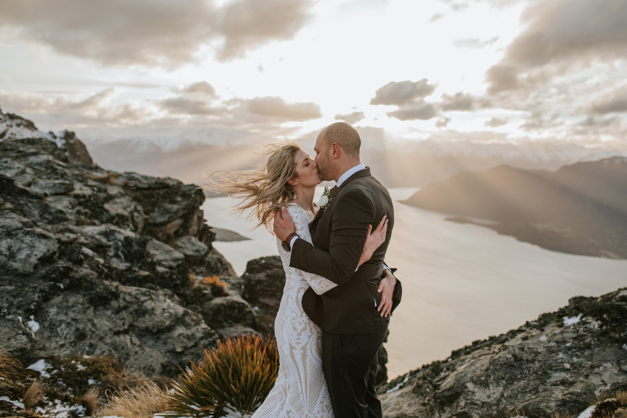 A bride and groom kiss on a mountain top. The sun is setting behind them, and rays of light descend from the clouds. There are snow capped mountains and a lake in the background.