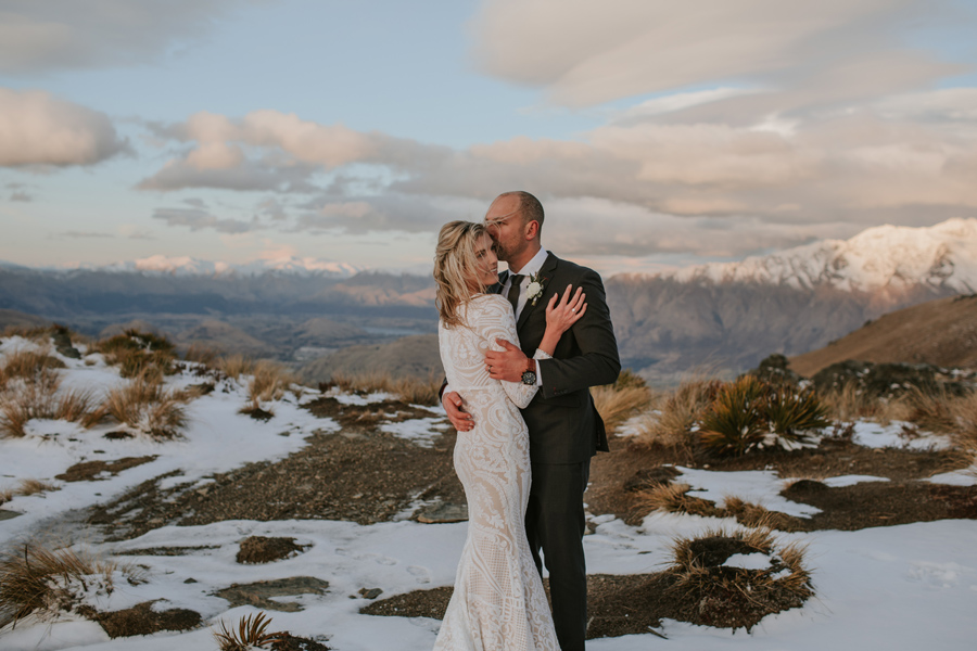 A groom kisses his bride on the side of her head. They are standing on a mountain top as the sun sets, and a soft glow is cast over them. There are snowy mountains in the background.
